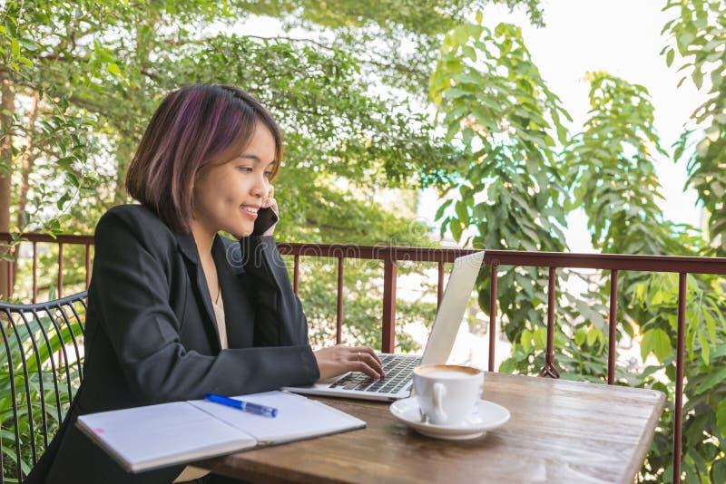 Junge Frau, die an Laptop Gartenansicht in der im Freien arbeitet stockfoto