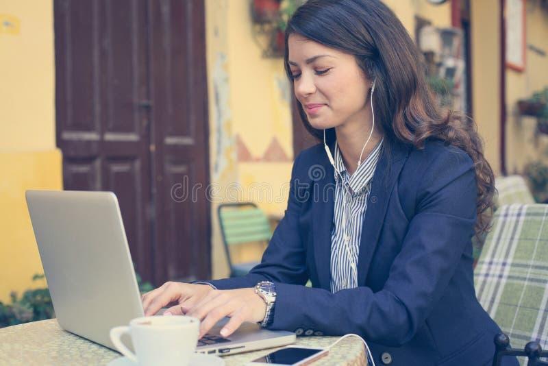 Junge Frau, die an Laptop, hörende Musik arbeitet lizenzfreie stockbilder