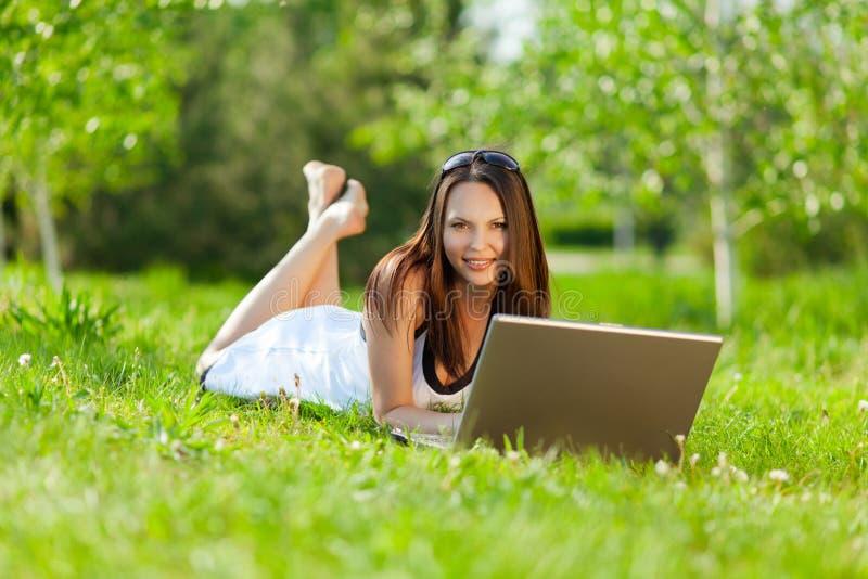 Junge Frau, die Laptop im Park verwendet stockbild