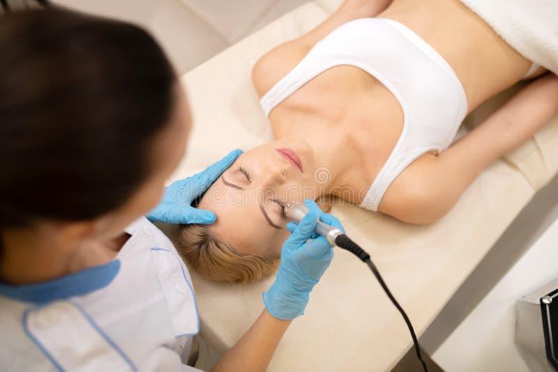 Junge Frau, die Laser-Hautbehandlung im Sch?nheitssalon hat lizenzfreie stockfotografie