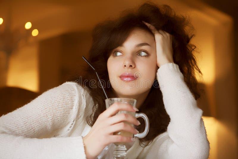 Junge Frau, die latte Kaffee im Kaffee genießt lizenzfreie stockfotos