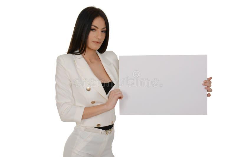Junge Frau, die leeres Schild oder Kopieraum für Slogan oder Text, über weißem Hintergrund zeigt lizenzfreie stockfotos