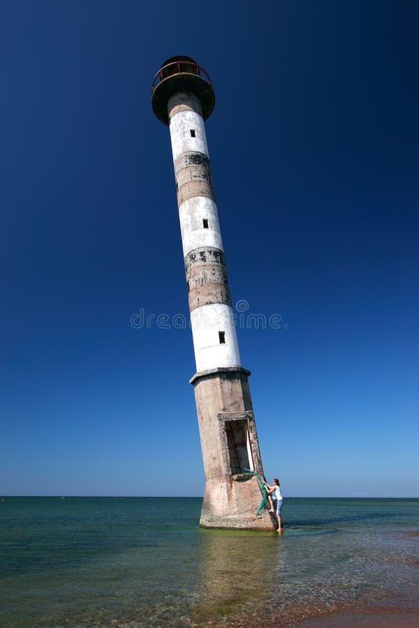 Junge Frau, die in Leuchtturm steigt. stockfotos