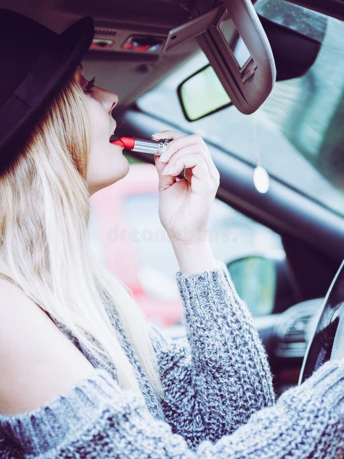 Junge Frau, die Lippenstift im Auto anwendet lizenzfreies stockfoto
