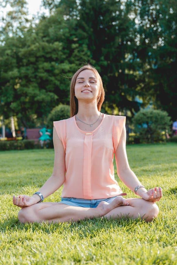 Junge Frau, die in Lotussitz auf Natur sitzt stockfoto