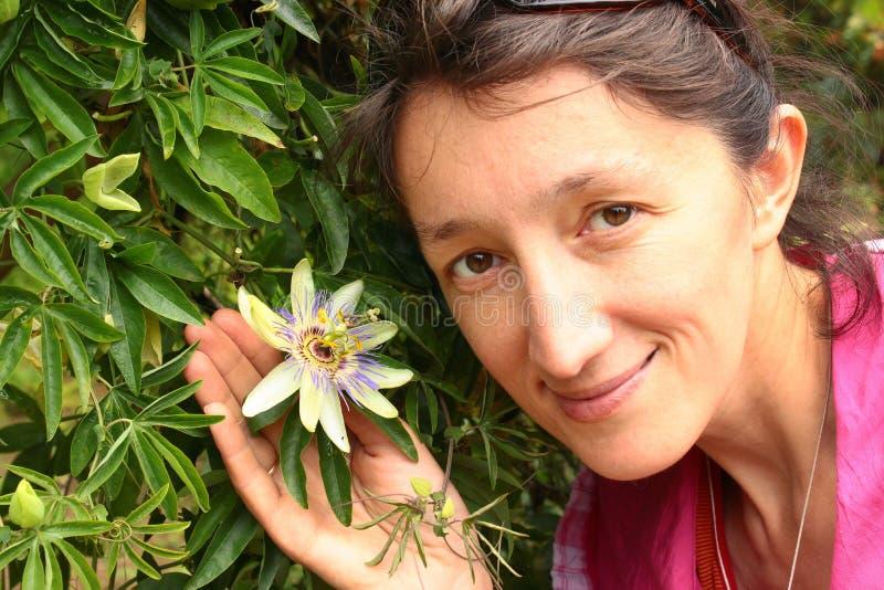 Junge Frau, die Maracujablume hält lizenzfreie stockfotos