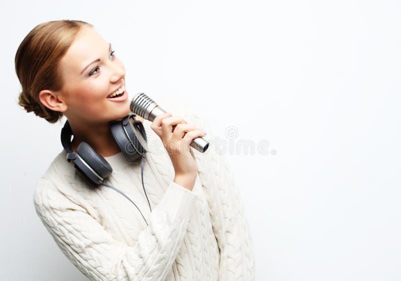 Junge Frau, die an in Mikrofon mit Kopfhörern im Studio singt stockbild
