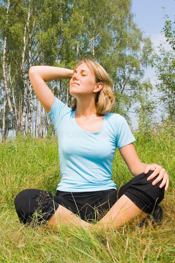 Junge Frau, die mit überkreuzten Beinen und entspannt sitzt stockbild