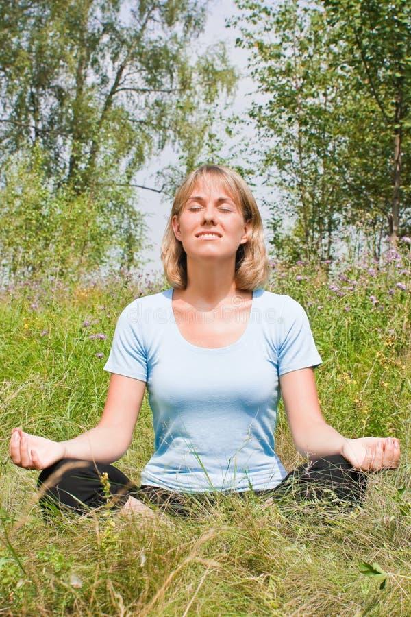 Junge Frau, die mit überkreuzten Beinen und entspannt sitzt stockfoto