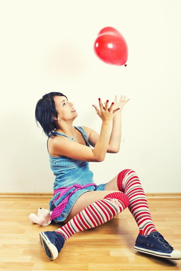 Junge Frau, die mit Ballon spielt lizenzfreie stockbilder
