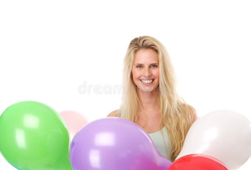 Junge Frau, die mit bunten Ballonen lächelt stockbilder