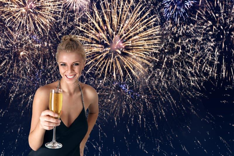 Junge Frau, die mit Champagner in ihren Händen feiert stockbild