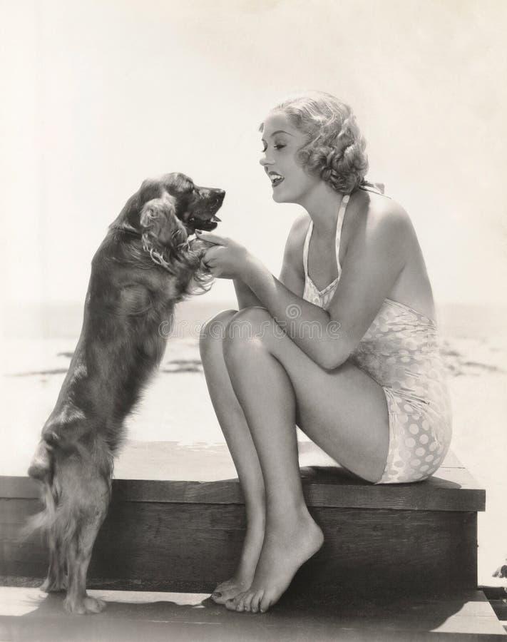 Junge Frau, die mit Cocker spaniel am Strand spielt lizenzfreies stockbild