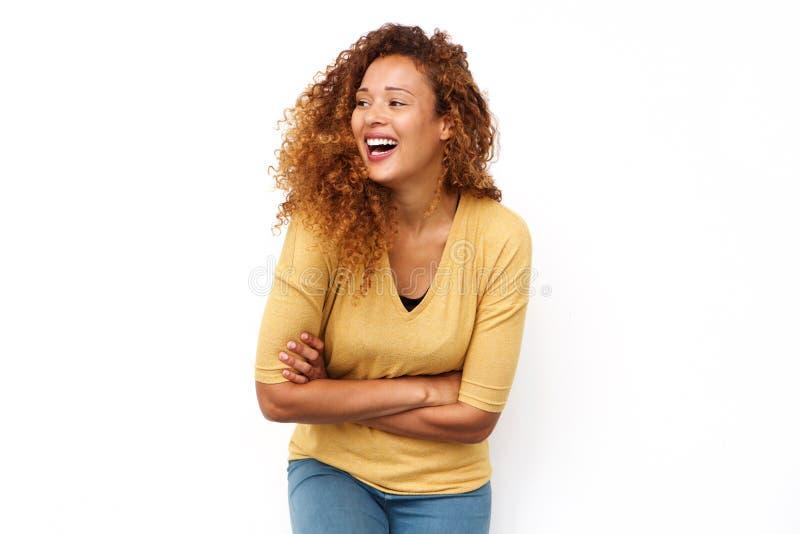 Junge Frau, die mit den Armen gekreuzt gegen lokalisierten weißen Hintergrund lacht lizenzfreies stockfoto