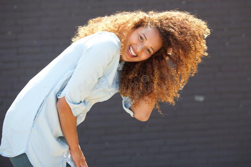 Junge Frau, die mit der Hand im Haar durch graue Wand lacht stockbilder