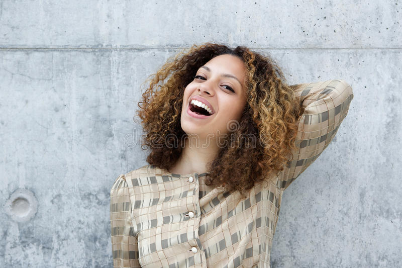 Junge Frau, die mit der Hand im Haar lächelt stockfotografie