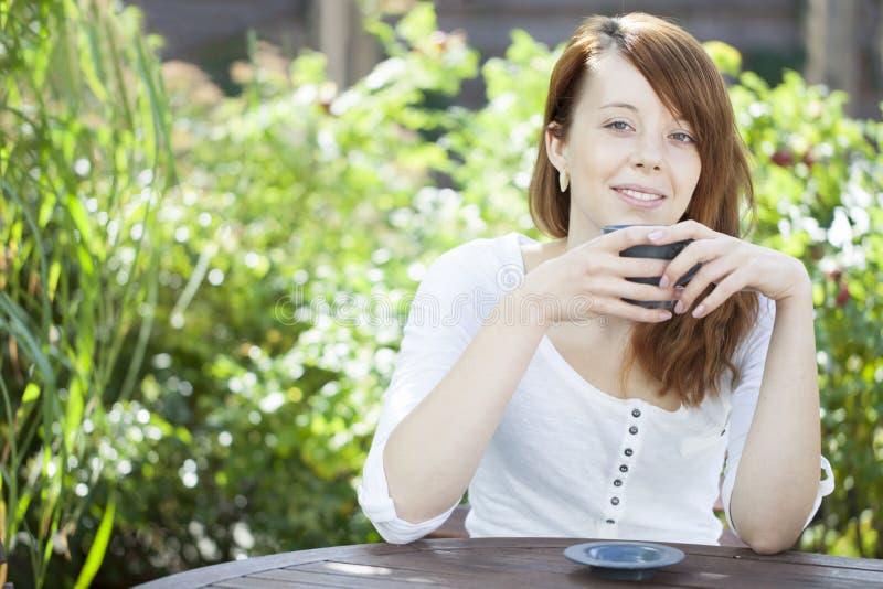 Junge Frau, die mit einem Becher Kaffee sich entspannt stockbilder