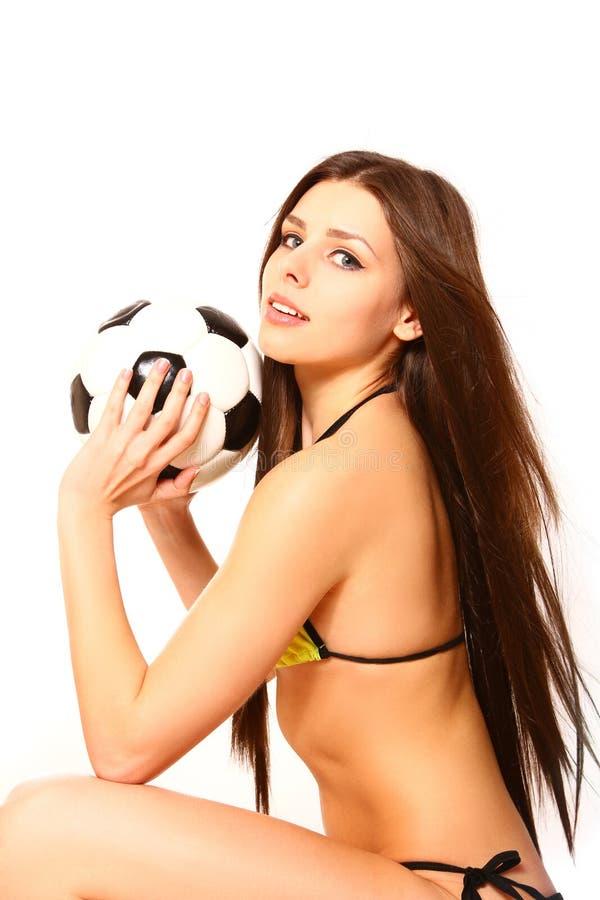 Junge Frau, die mit einem Fußball auf einem weißen Hintergrund aufwirft lizenzfreie stockbilder