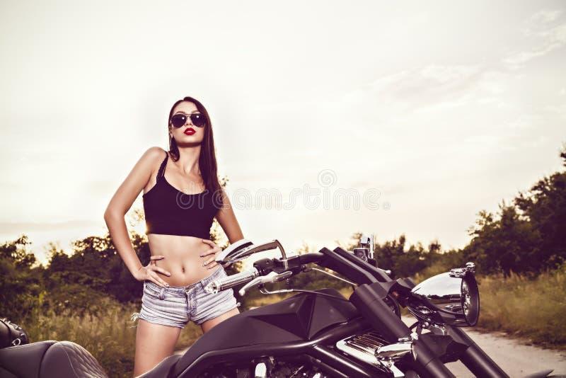 Junge Frau, die mit einem Motorrad aufwirft stockfotos