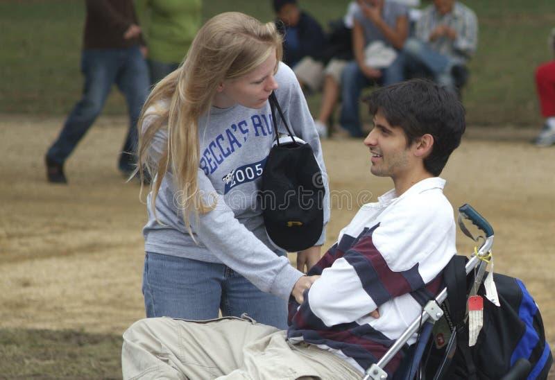 Junge Frau, die mit einem Rollstuhlgrenzjungen Mann spricht stockbilder