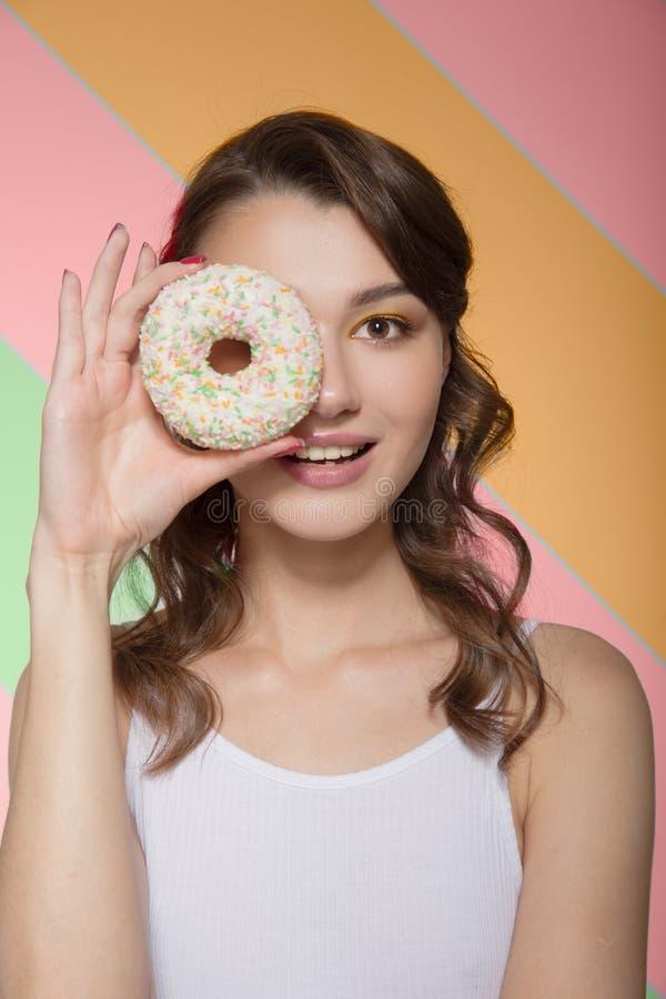 Junge Frau, die mit einem süßen Donut in ihren Händen lächelt Porträt auf einem Farbhintergrund stockbild