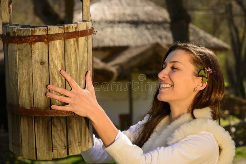 Junge Frau, die mit einem Stapel des Wassers spielt lizenzfreies stockbild