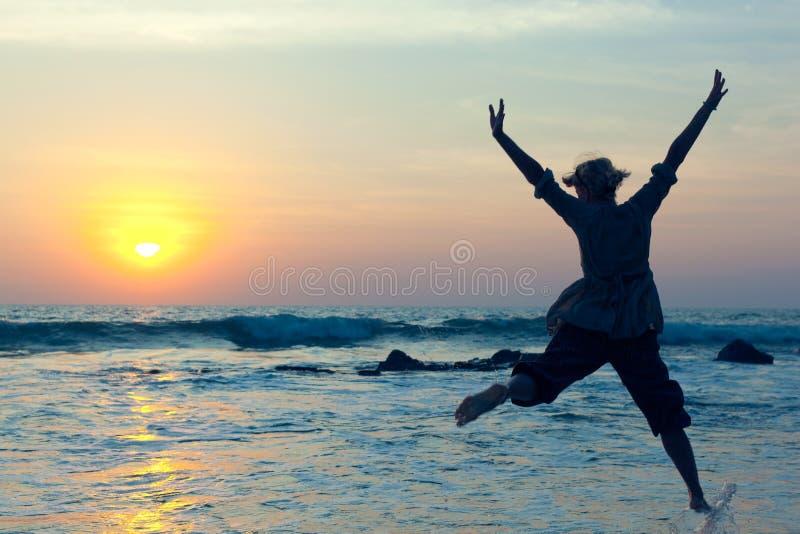 Junge Frau, die mit Freude über dem Wasser springt lizenzfreie stockfotos