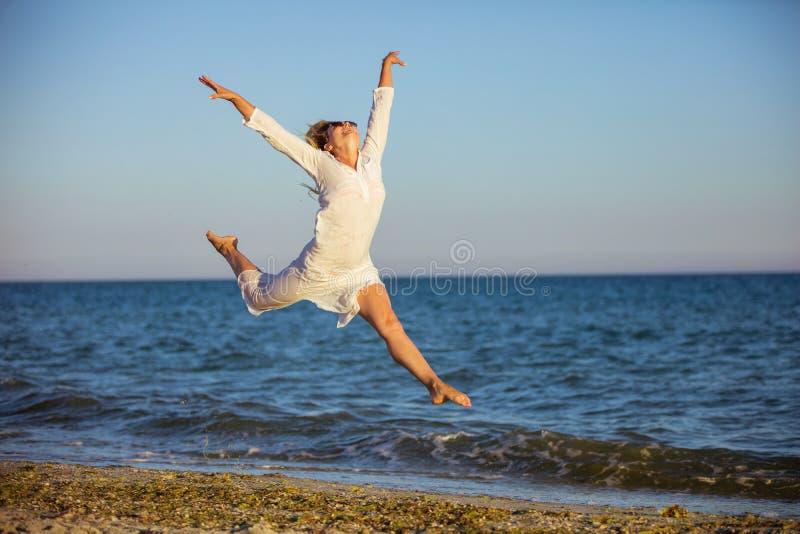 Junge Frau, die mit Freude auf Strand springt lizenzfreie stockfotografie