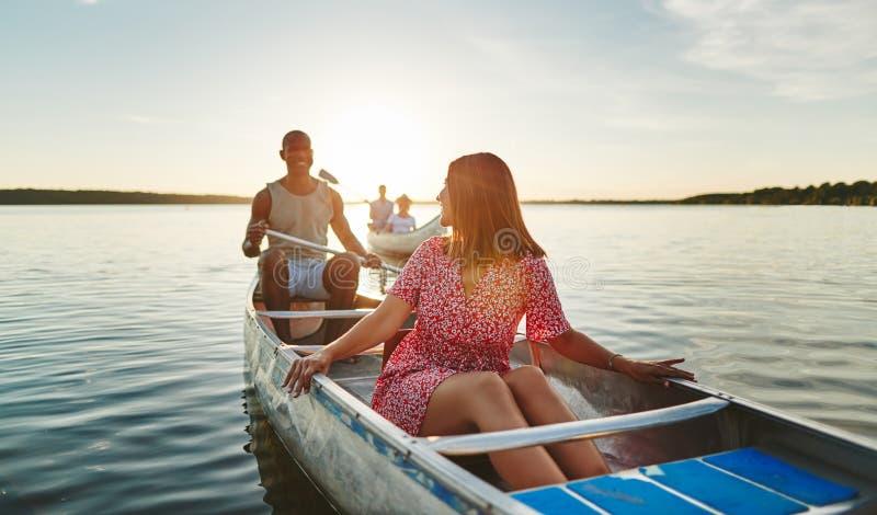 Junge Frau, die mit Freunden an einem Sommernachmittag canoeing ist stockfoto