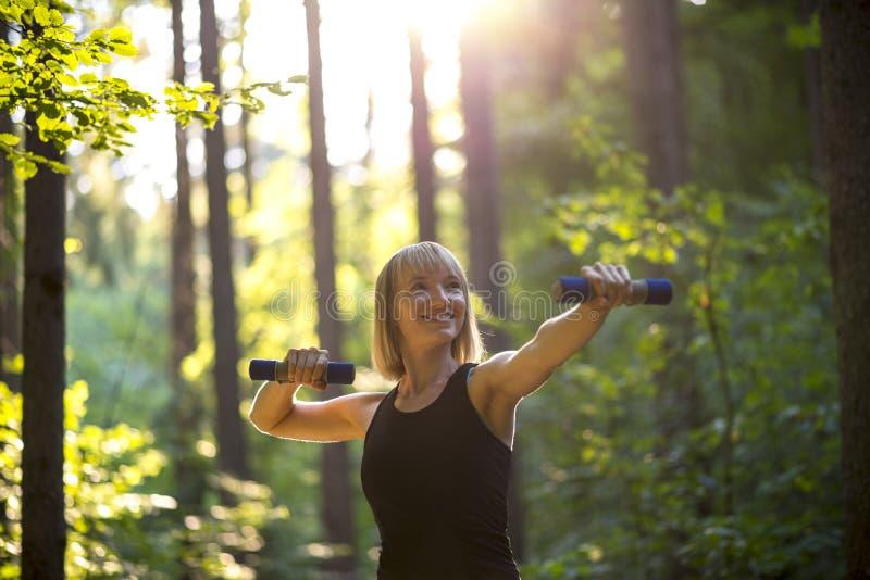Junge Frau, die mit Gewichten ausarbeitet stockbild