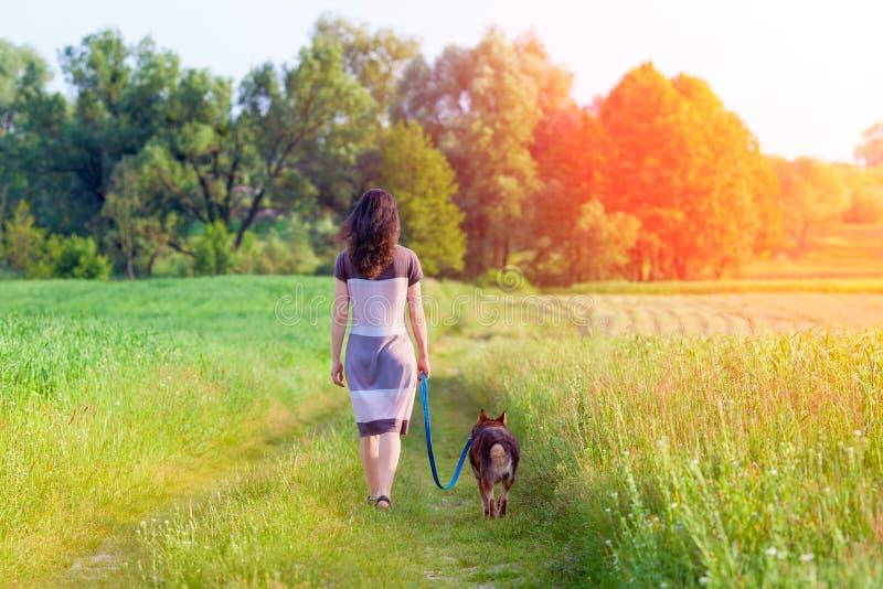 Junge Frau, die mit Hund geht lizenzfreies stockbild