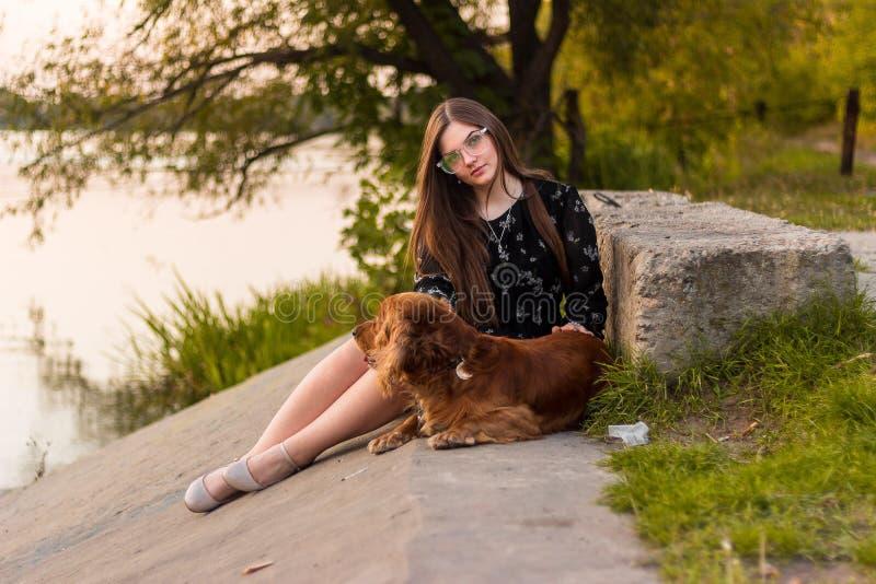 Junge Frau, die mit ihrem Hund genießt Sonnenuntergang sitzt lizenzfreie stockfotos