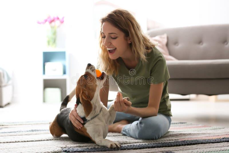 Junge Frau, die mit ihrem Hund spielt lizenzfreies stockfoto