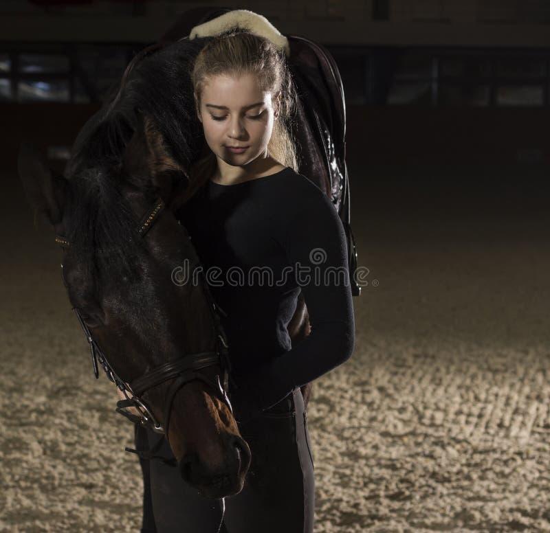 Junge Frau, die mit ihrem Pferd steht stockfoto