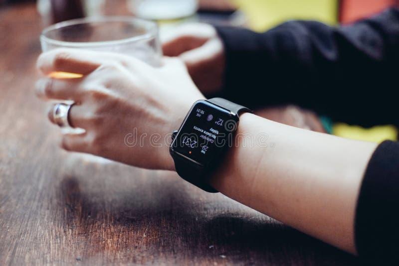 Junge Frau, die mit intelligenter Uhr an der Bar trinkt stockfotografie