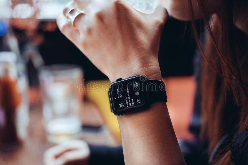 Junge Frau, die mit intelligenter Uhr an der Bar trinkt lizenzfreies stockfoto
