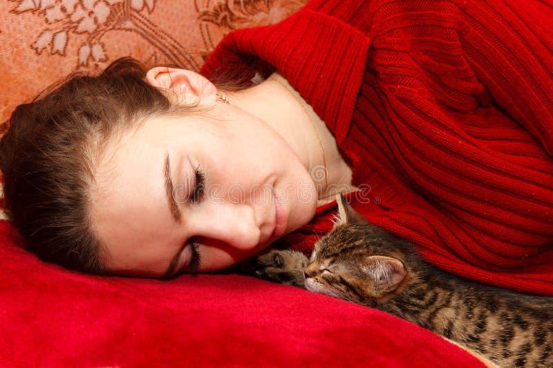 Junge Frau, die mit Kätzchen schläft stockbild