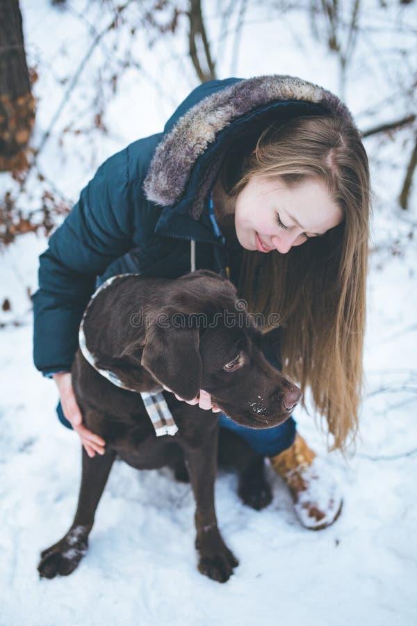 Junge Frau, die mit Labrador-Hund im Winter geht stockbild