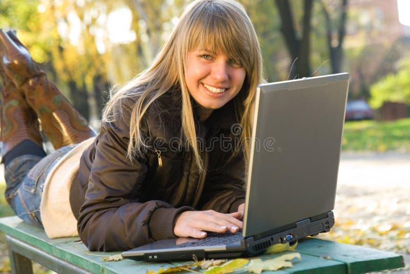 Junge Frau, die mit Laptop im Stadtpark arbeitet stockfotos