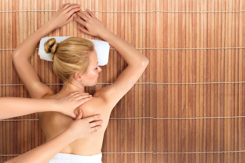 Junge Frau, die mit Massage im Badekurort sich entspannt lizenzfreie stockfotografie