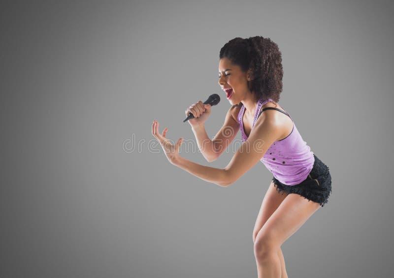 Junge Frau, die mit Mikrofon gegen grauen Hintergrund singt lizenzfreie abbildung