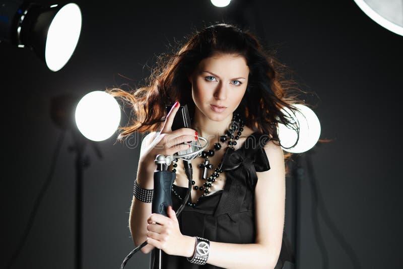 Junge Frau, die mit Mikrofon singt stockbilder