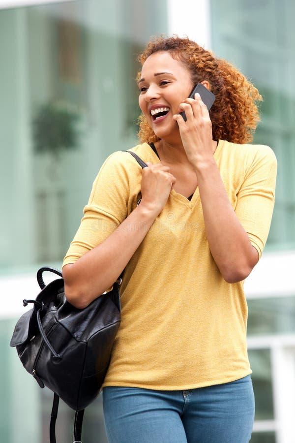 Junge Frau, die mit Mobiltelefon in der Stadt geht und spricht lizenzfreies stockbild