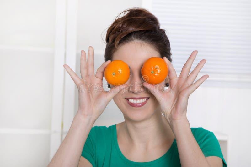 Junge Frau, die mit orange Augen lächelt. stockbilder