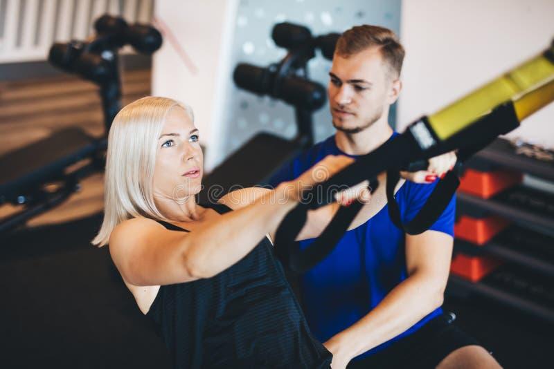 Junge Frau, die mit persönlichem Trainer trainiert stockbild