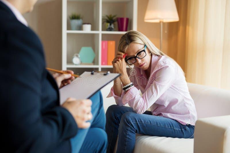 Junge Frau, die mit Psychotherapeuten spricht stockfotografie