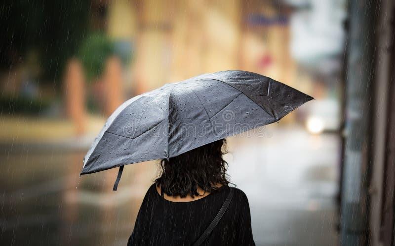 Junge Frau, die mit Regenschirm am Herbsttag geht lizenzfreie stockfotos