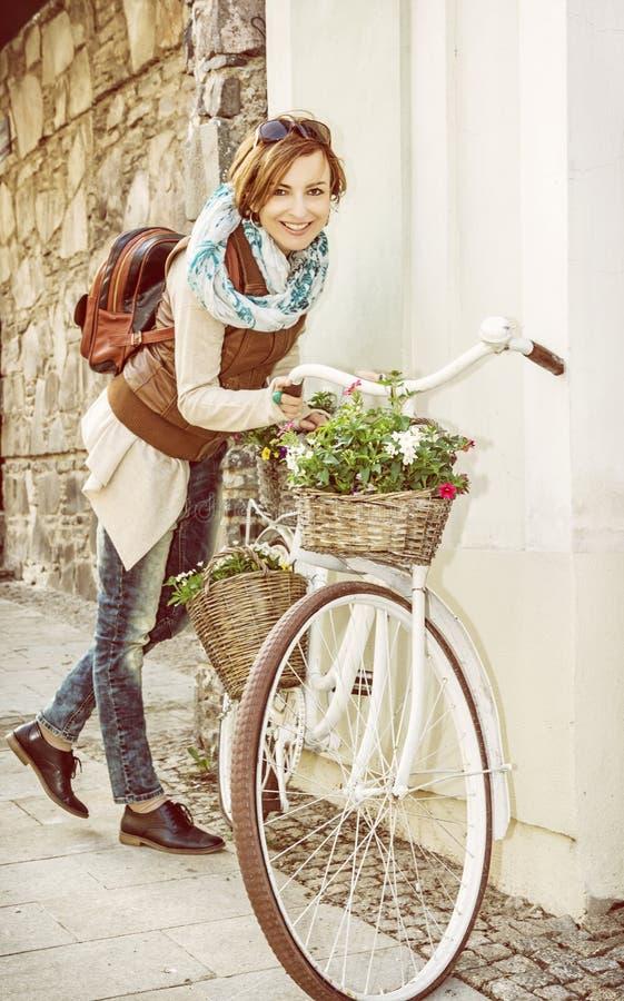 Junge Frau, die mit Retro- Fahrrad, gelber Filter aufwirft stockfotos