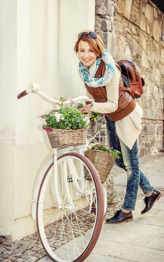 Junge Frau, die mit Retro- Fahrrad, gelber Filter aufwirft stockfotografie