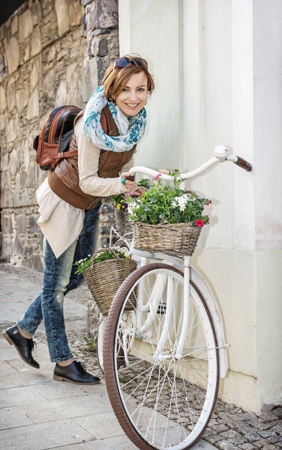 Junge Frau, die mit Retro- Fahrrad mit Weidengartenkörben aufwirft lizenzfreies stockfoto